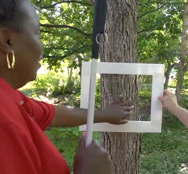 a woman is reaching through a picture frame which is held up to a tree trunk. She is tracing the side of the tree trunk to see which part would be on the picture plane and what part of the trunk would be off the picture plane.